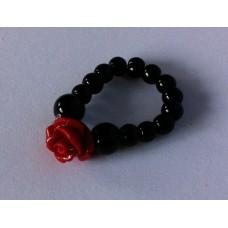 Ring van elastiek met zwarte kralen en een rood roosje.