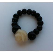 Ring van elastiek met zwarte kralen en een wit roosje.