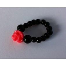 Ring van elastiek met zwarte kralen en een roze roosje